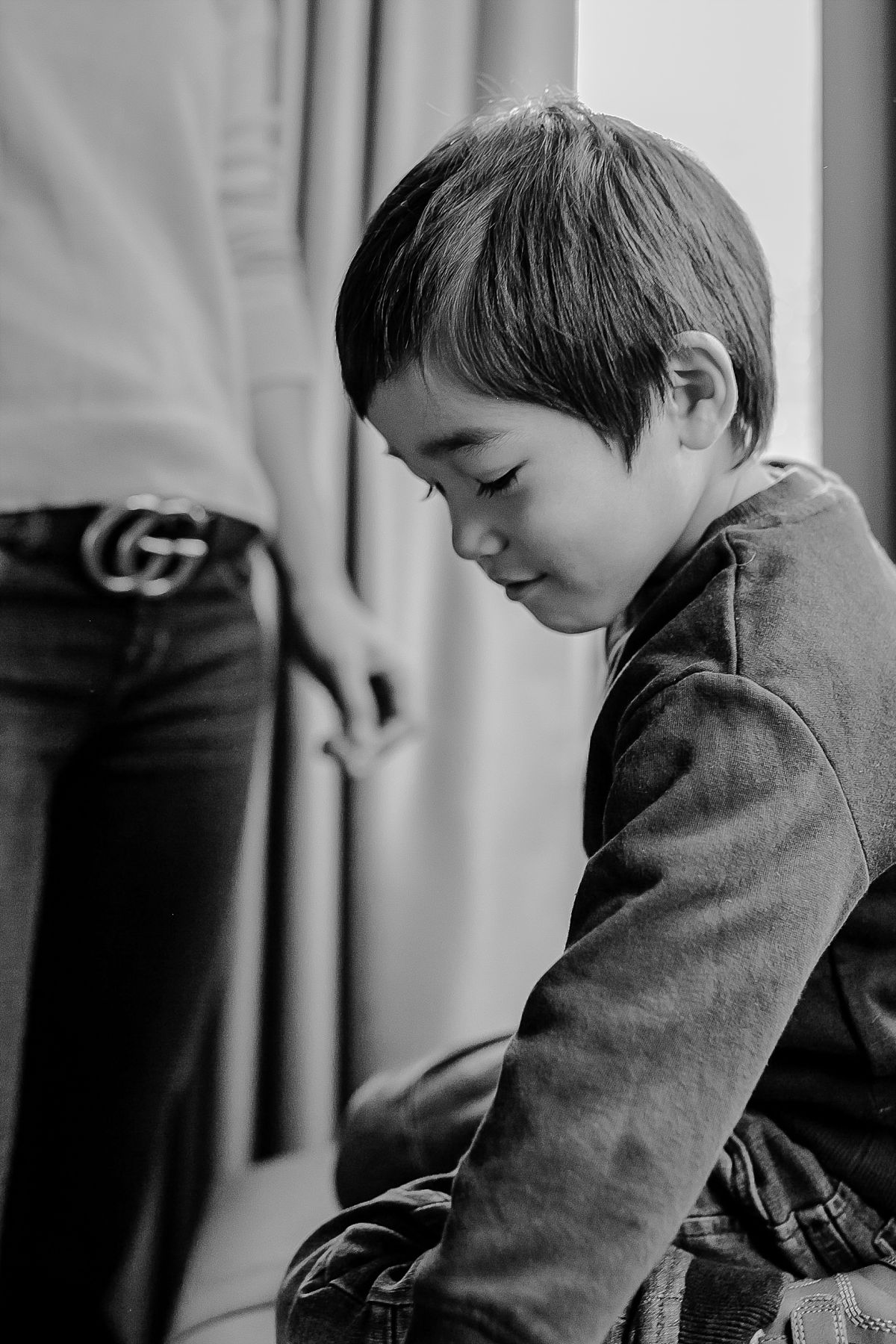 black and white portrait of three year boy playing with his sneakers. photo by nyc family photographer krystil mcdowall