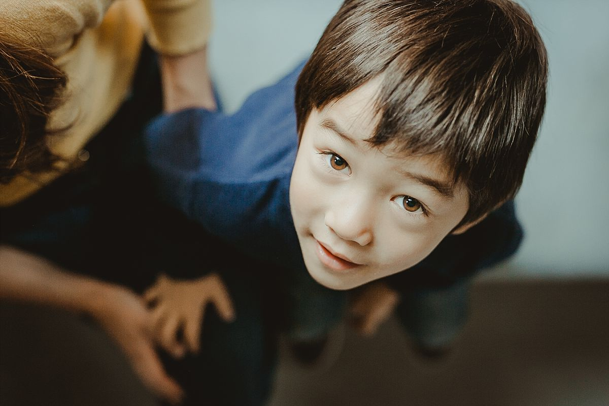 bird's eye view portrait of boy looking up at camera while sitting in his manhattan hotel while on family vacation with. krystil mcdowall photography captures candid family moments