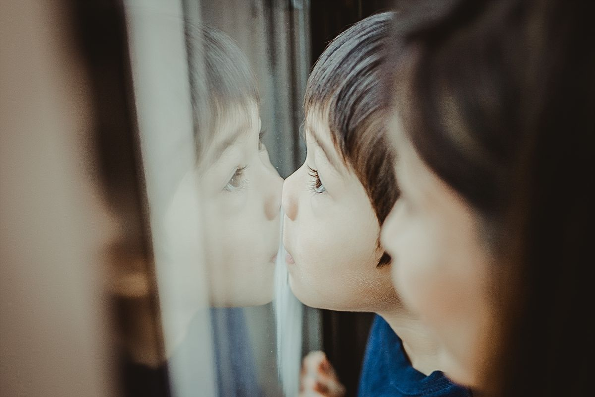 candid moment of mom and son steam writing on the window of their midtown manhattan hotel. krystil mcdowall photography captures candid family moments