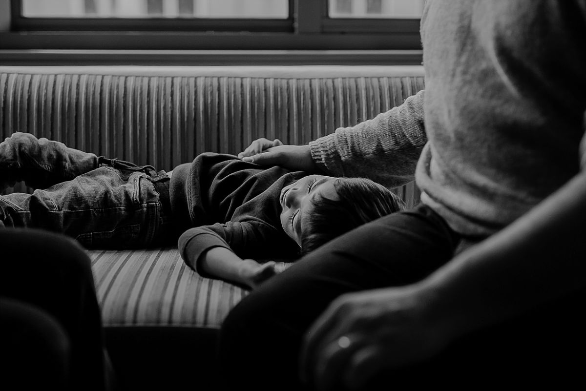 candid photo of son on hotel sofa lounge all exhausted after playing with mom and dad. photo by nyc family photographer krystil mcdowall
