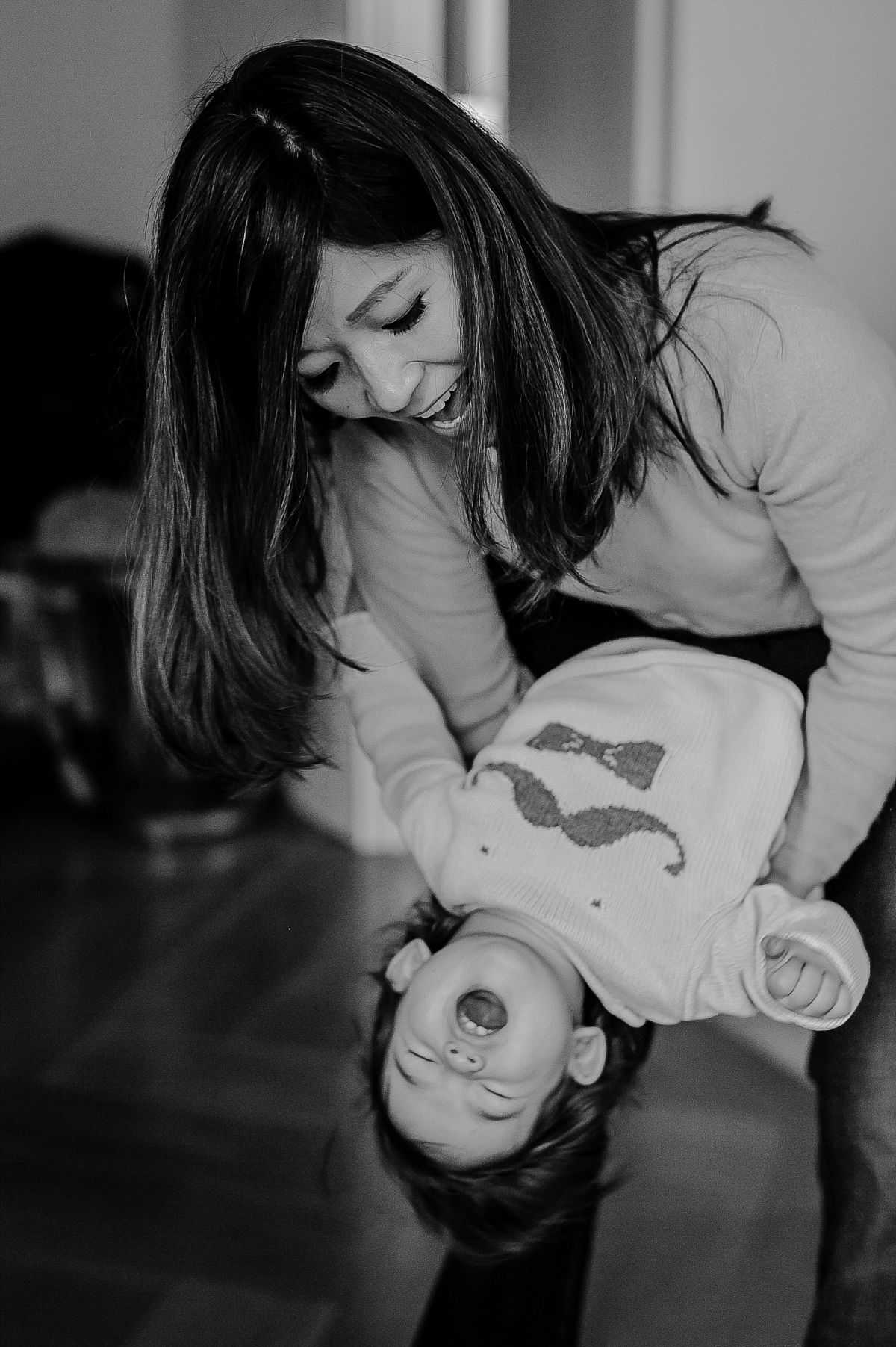 mom throwing daughter round and making daughter laugh during candid family photo session in nyc. image by nyc family photographer krystil mcdowall