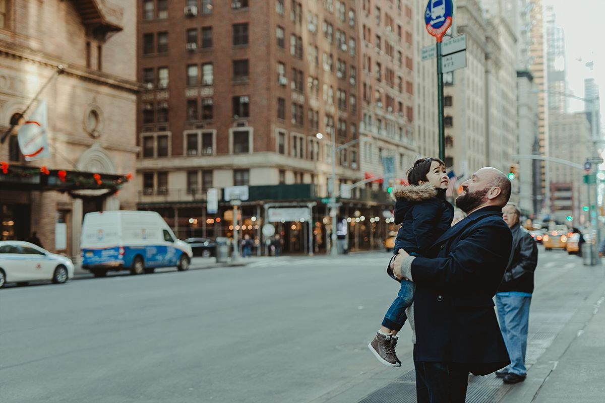 dad and son exploring the streets and buildings of manhattan during candid family photo session in nyc. image by nyc family photographer krystil mcdowall