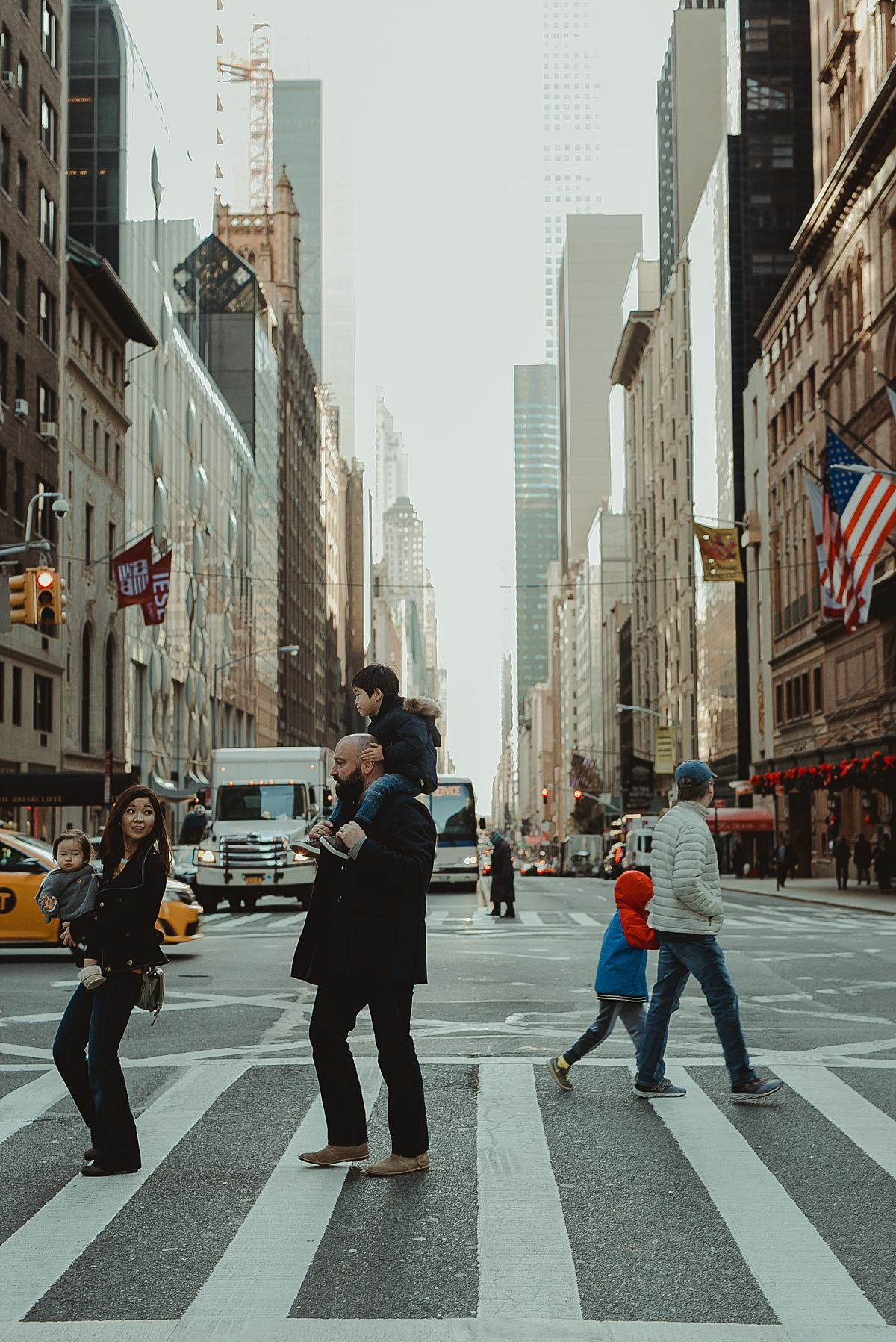 family of four walking across the streets of midtown with skyscraper buildings in the background. image taken by krystil mcdowall photography