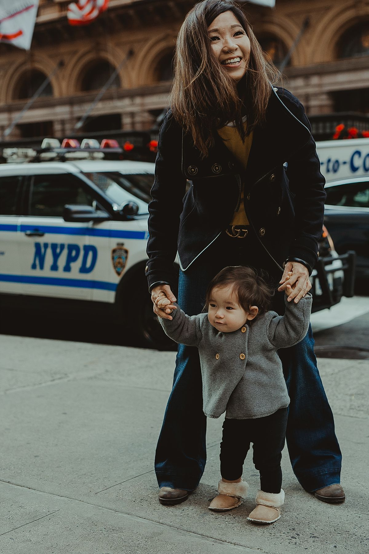mom and daughter walking the streets of midtown with nypd car in the background. image taken by photographer krystil mcdowall