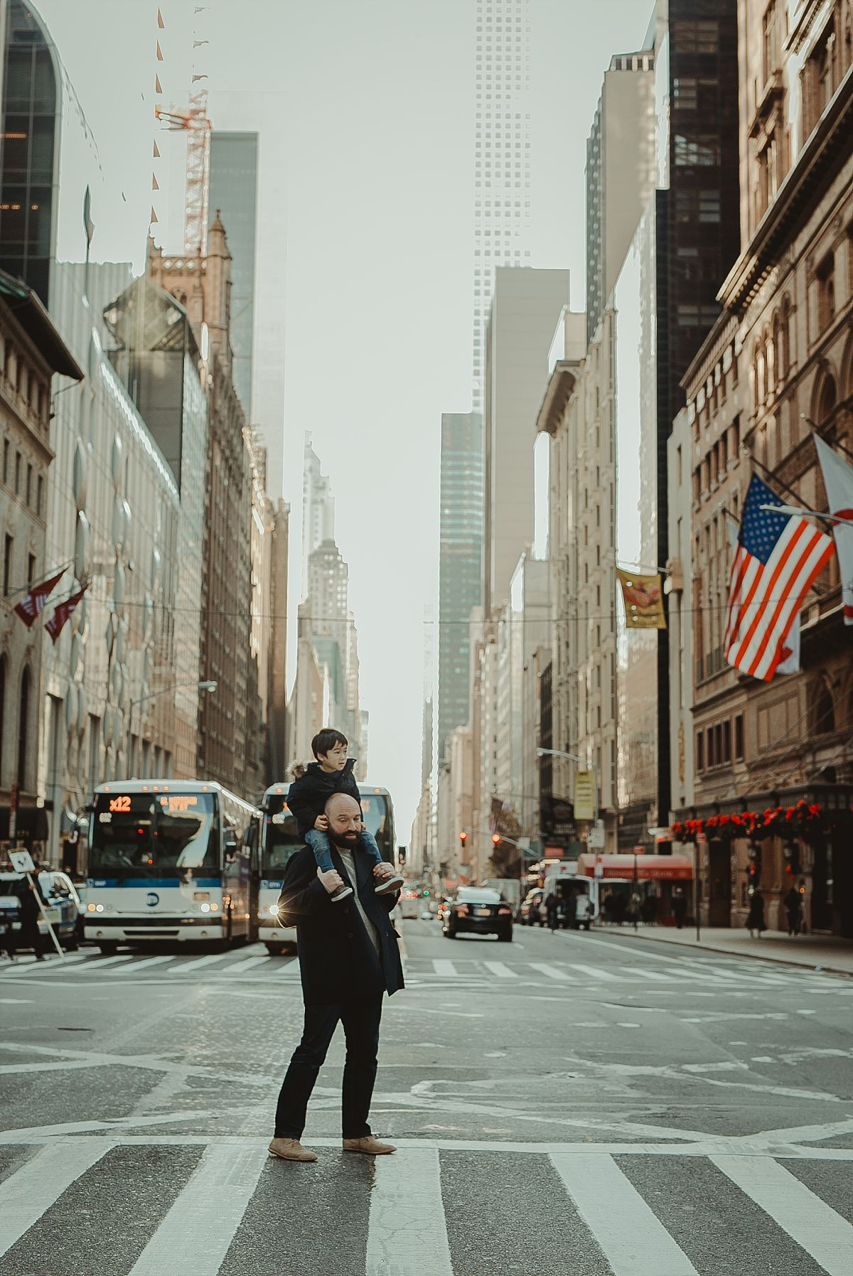 dad and son walking the streets of midtown with skyscraper buildings in the background. image taken by photographer krystil mcdowall