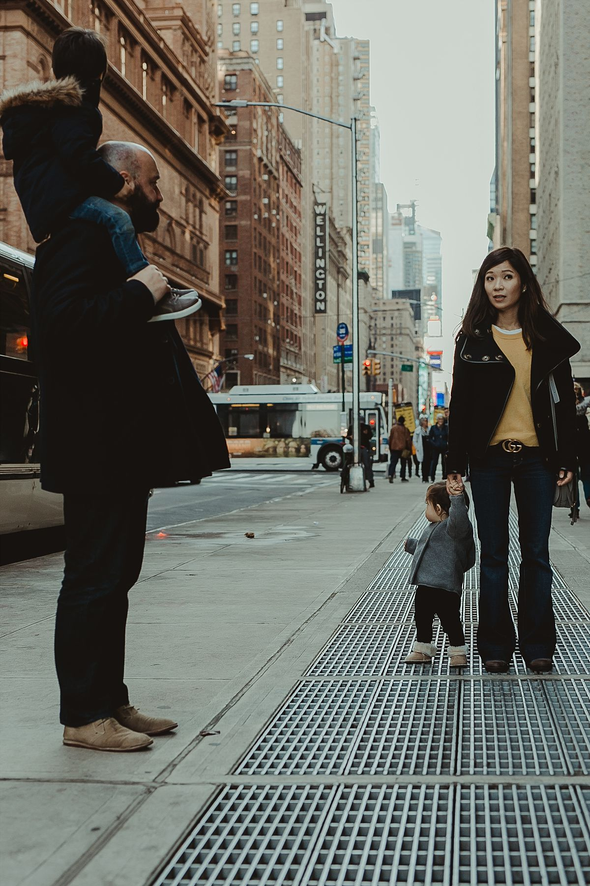 candid image of family of four walking the streets of midtown manhattan on a cold winter's day. image by nyc family photographer krystil mcdowall