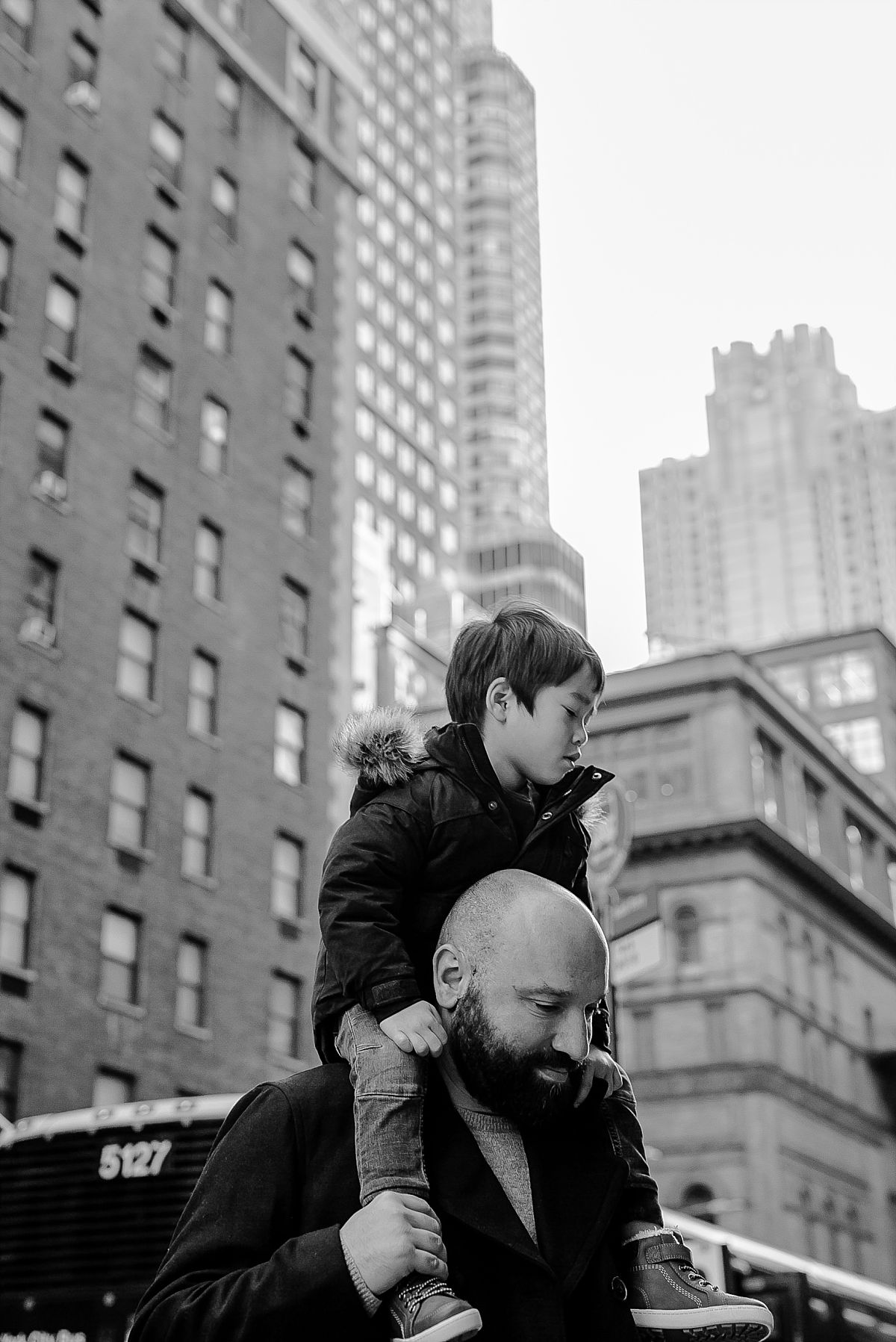 dad gives young son a shoulder ride as he walks through the streets of midtown manhattan. image by nyc family photographer krystil mcdowall