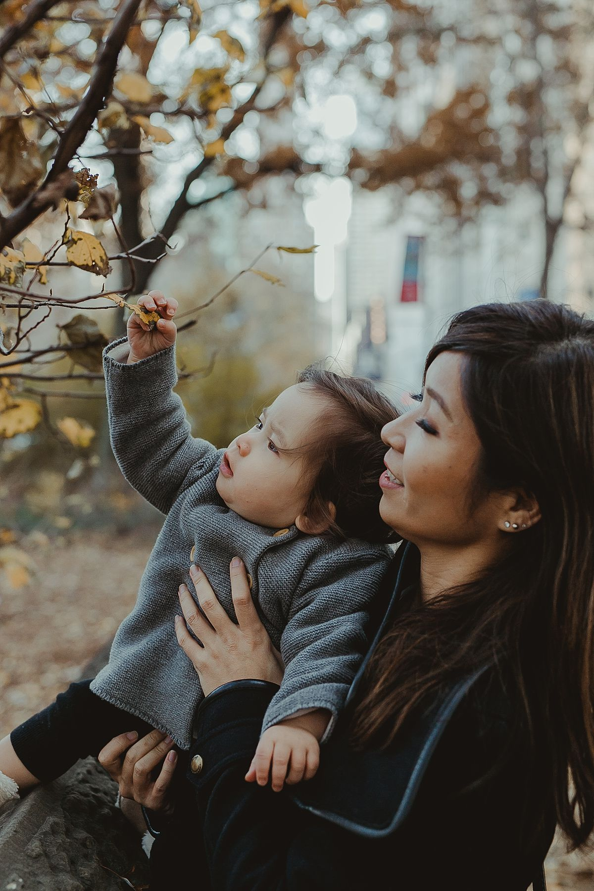 mom and daughter playing with tree leaves at the bottom of central park on chilly winters day. photo by nyc family photographer krystil mcdowall