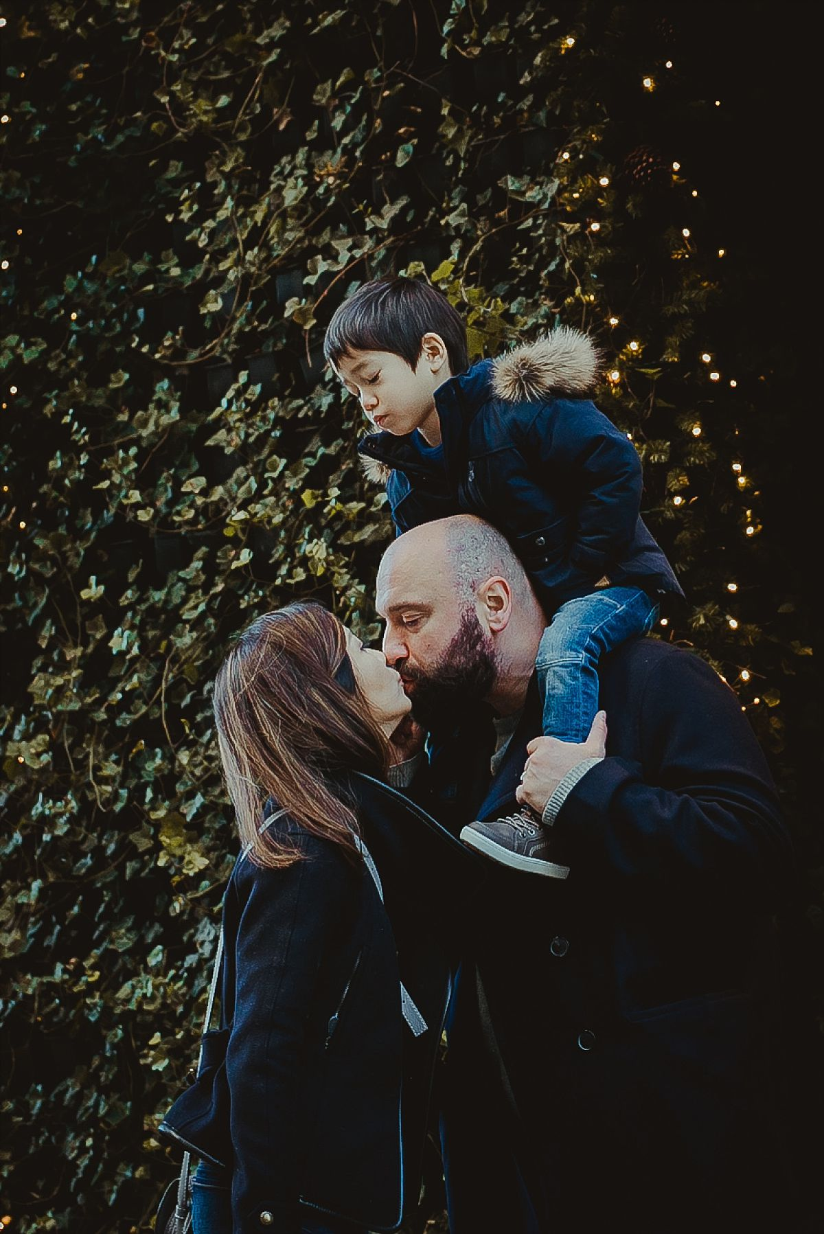 mom kissing dad while son enjoys shoulder ride from dad during family photo session in nyc. photo by nyc family photographer krystil mcdowall