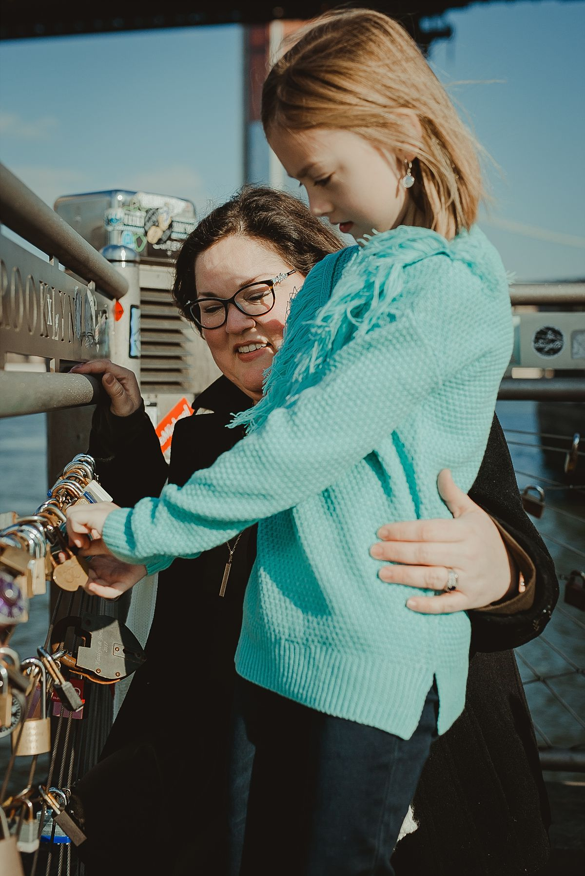 candid mom and daughter portrait as they explore the lockets at pier in dumbo brooklyn. photo by nyc family photographer krystil mcdowall