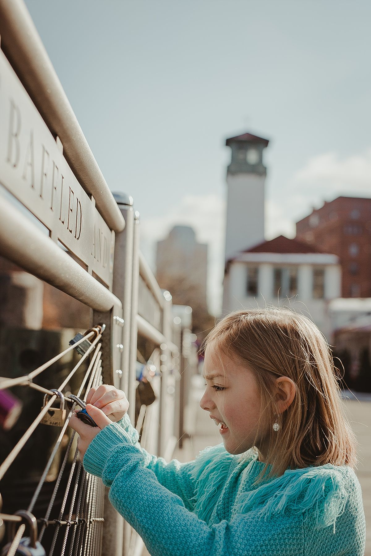 photo of girl as she looks at the lockets at pier in dumbo brooklyn. photo by nyc family photographer krystil mcdowall