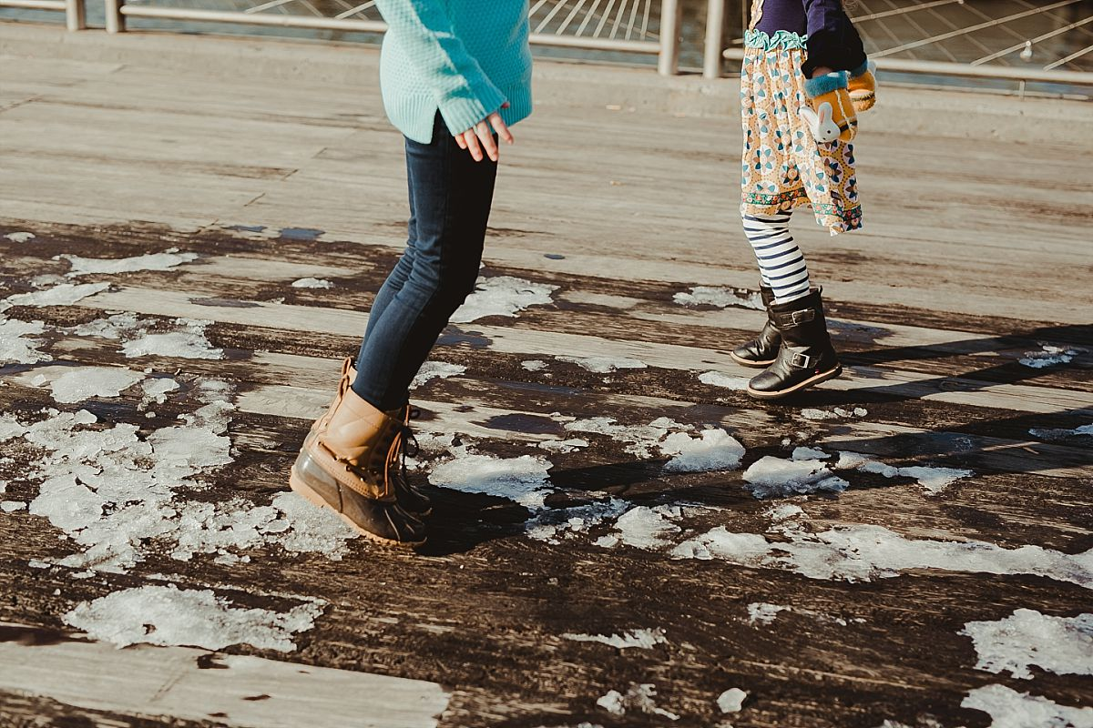 photo of sisters stomping their feet in the snow at the pier in dumbo. photo by krystil mcdowall photography