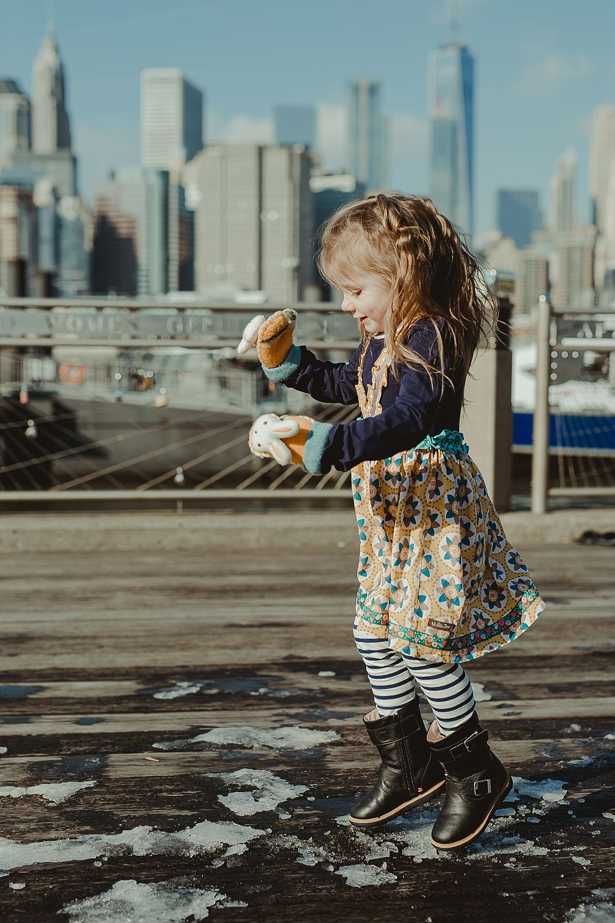 portrait of girl in striped leggings stomping in the snow at the pier at dumbo with the nyc skyline in the background. photo by nyc family photographer krystil mcdowall