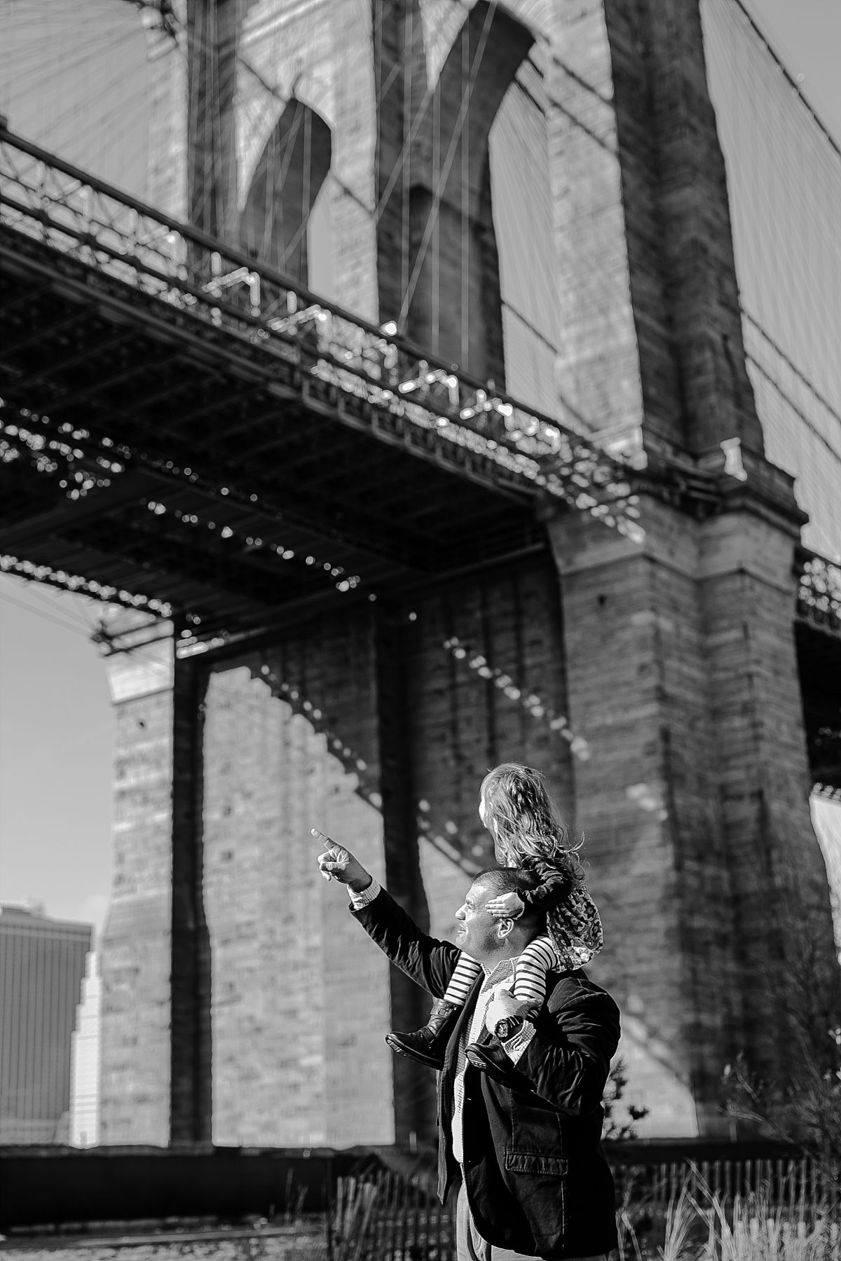 black and white image of dad giving daughter a shoulder ride in front of the brooklyn bride in dumbo brooklyn. photo by nyc family photographer krystil mcdowall
