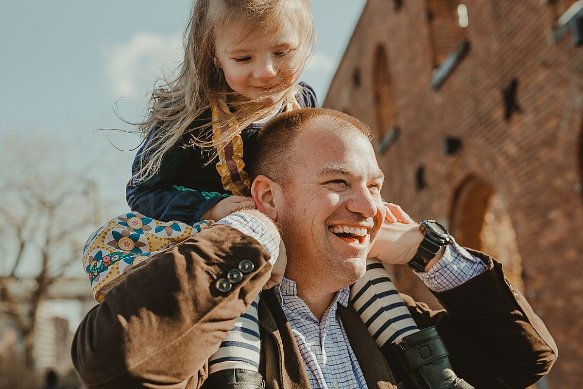 dad laughs while giving daughter a shoulder ride in front of the brooklyn bride in dumbo brooklyn. photo by nyc family photographer krystil mcdowall