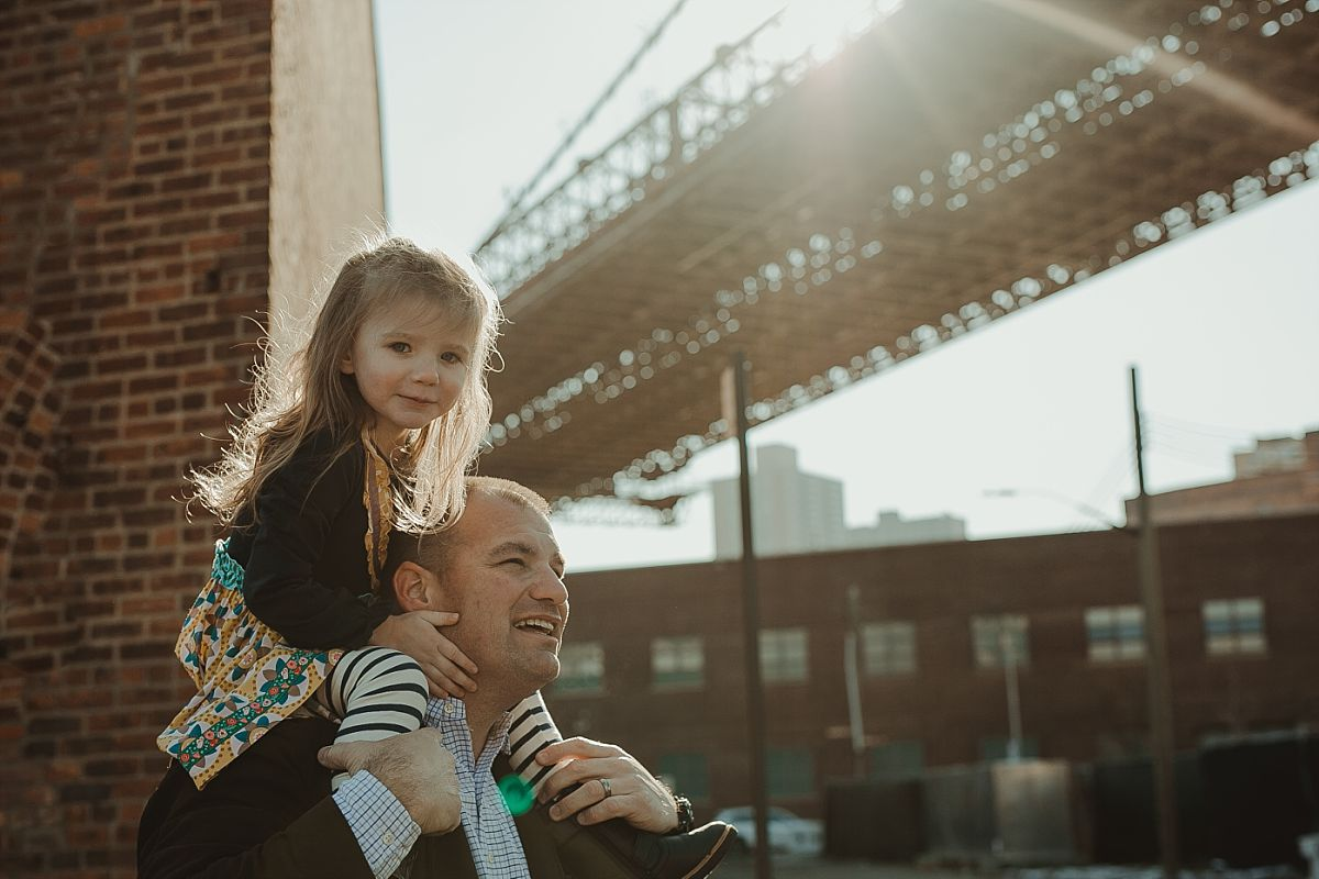 daughter gets shoulder ride from dad near the brooklyn bride in dumbo brooklyn. photo by nyc family photographer krystil mcdowall