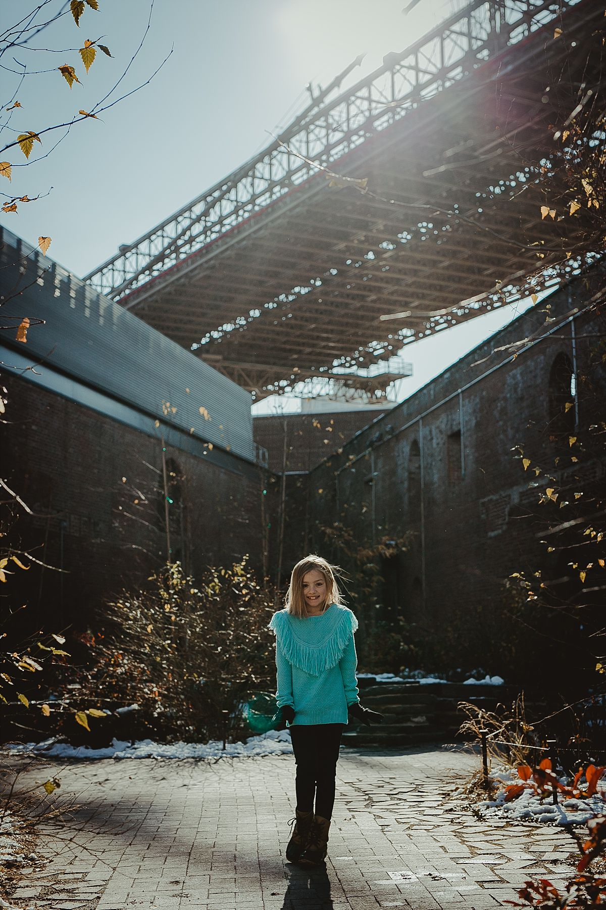 young girl poses in front of brooklyn bridge in dumbo brooklyn. capturing candid family photos is family photographer krystil mcdowall