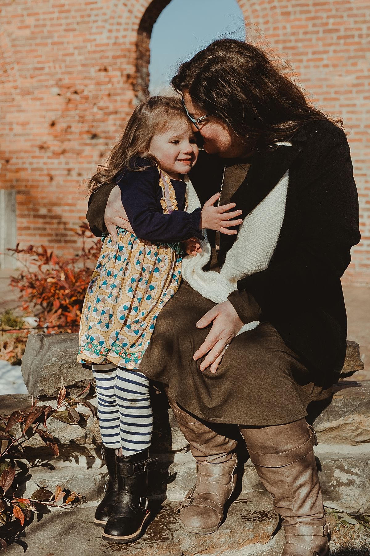 candid photo of mom and daughter cuddling with brick wall backdrop in dumbo brooklyn. image by nyc family photographer krystil mcdowall