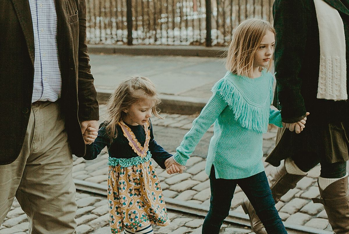 family of four walking along cobble stoned streets in brooklyn. documenting real memories for your family is krystil mcdowall photography