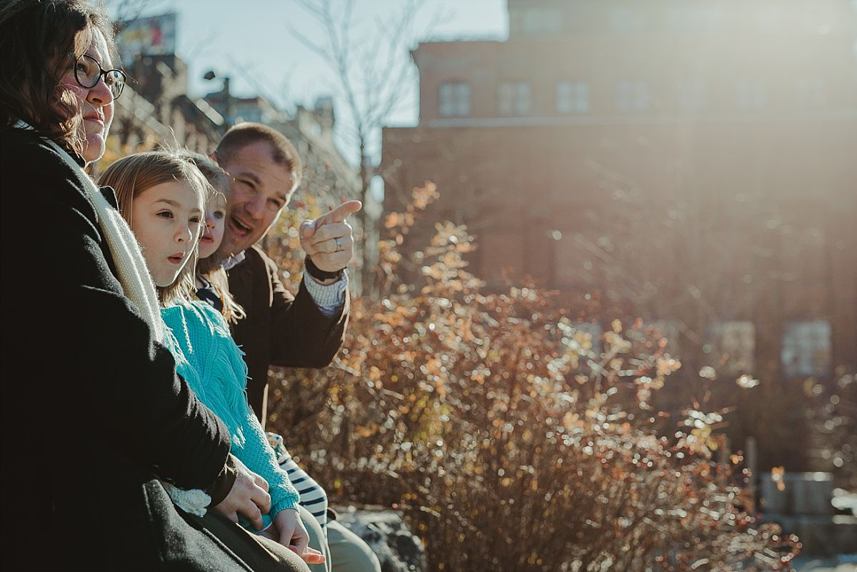 family sits in the sun with old industrial building in the background in brooklyn. documenting candid memories for your family is krystil mcdowall photography