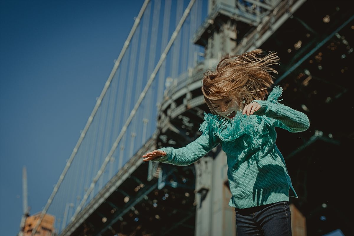 daughter in blue sweater gets thrown in the air by her dad in front of the manhattan bridge in brooklyn. image by nyc family photographer krystil mcdowall