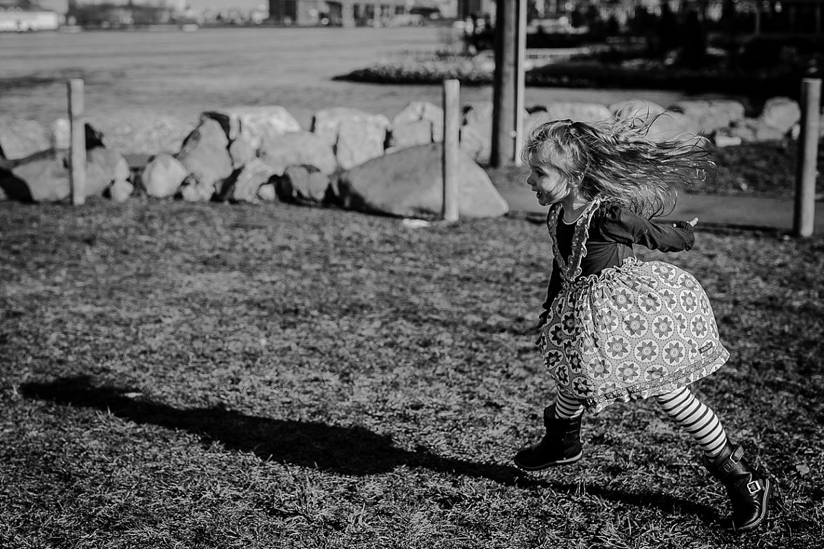 candid photo of daughter running around the grass in front of the manhattan bridge. image by nyc family photographer krystil mcdowall