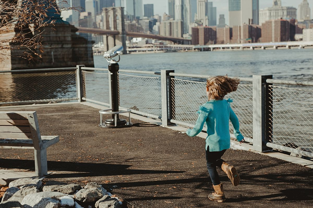 young girl in blue sweater runs along footpath in dumbo to one of the skyline lookouts located in front of the manhattan bridge. image by nyc family photographer krystil mcdowall