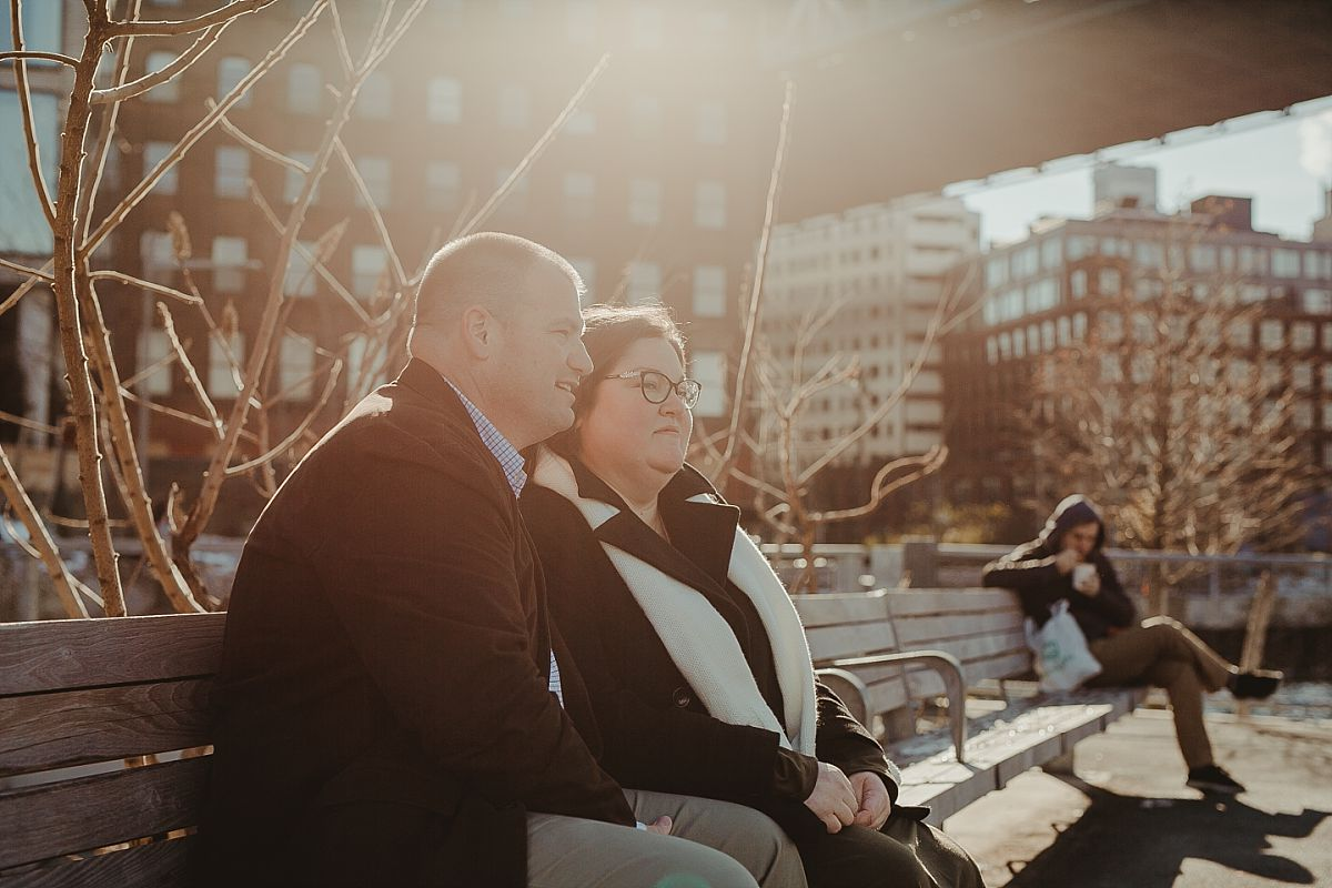 photo of mom and dad taking a rest on an nyc park bench with beautiful golden sun flare in the background. image by nyc family photographer krystil mcdowall