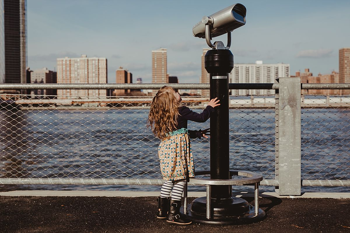 young girl looks up at lookout while playing on footpath. image by nyc family photographer krystil mcdowall