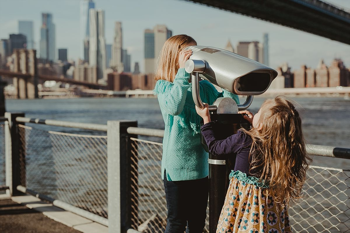 sisters play with footpath binoculars with the manhattan bridge and the nyc skyline in the background. image by nyc family photographer krystil mcdowall