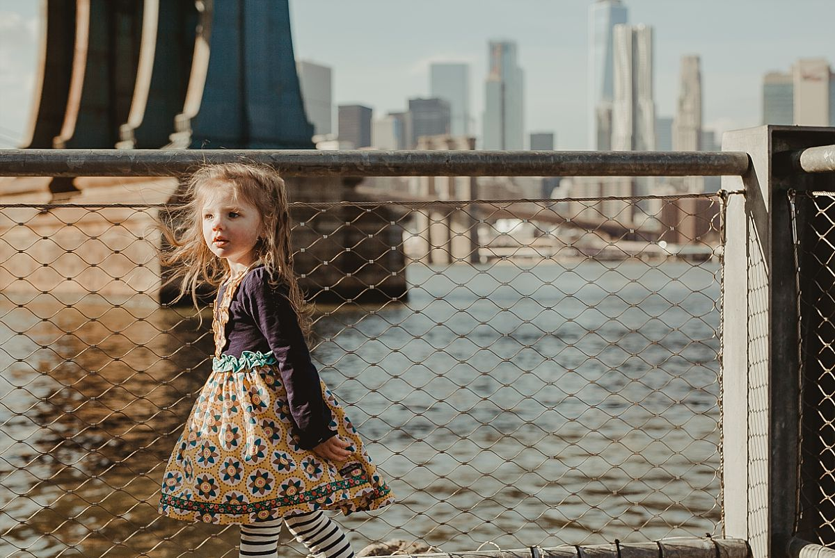 daughter plays on footpath in dumbo as the sun streams on her face and the manhattan bridge and the nyc skyline. image by nyc family photographer krystil mcdowall
