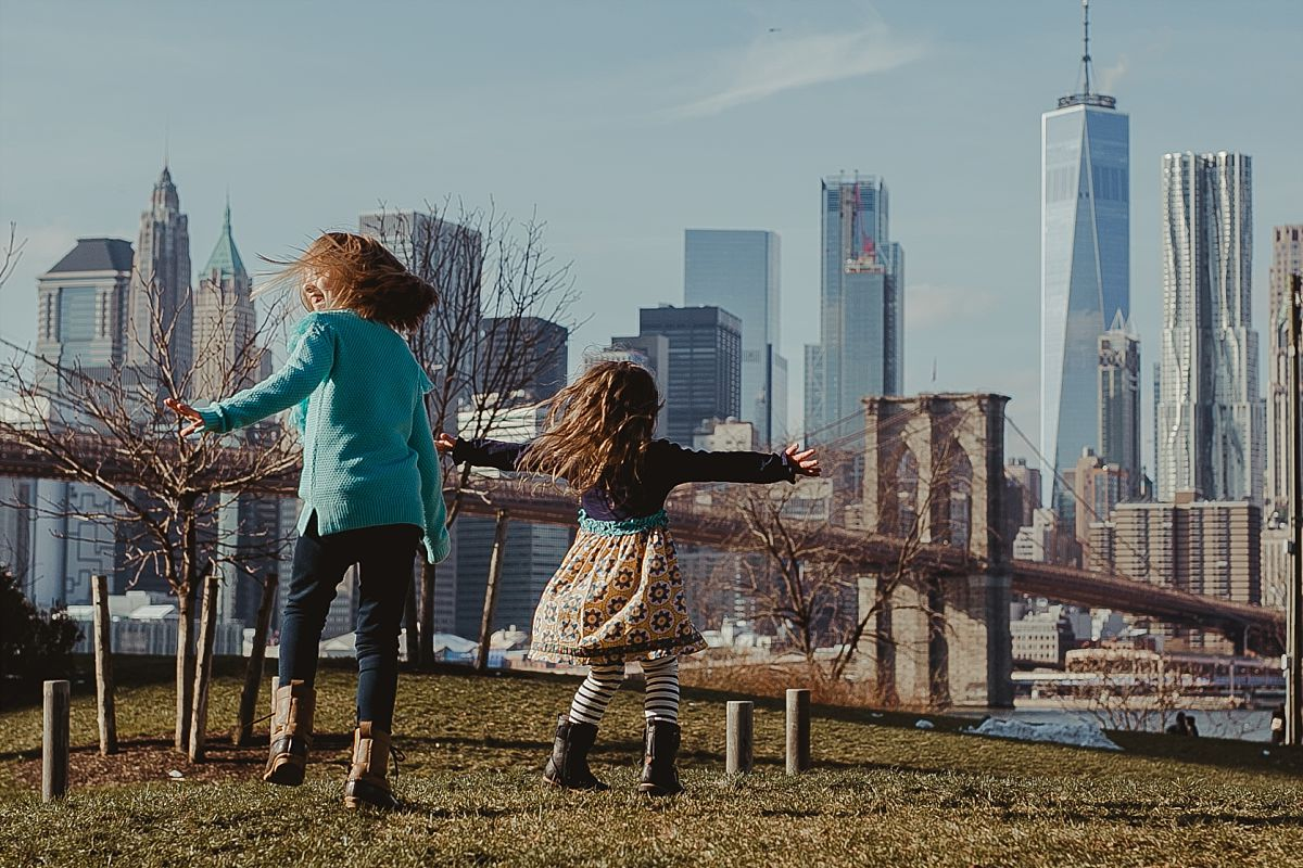 candid image of sisters dancing on green grass in brooklyn with iconic views of the nyc skyline in the background. image by nyc family photographer krystil mcdowall