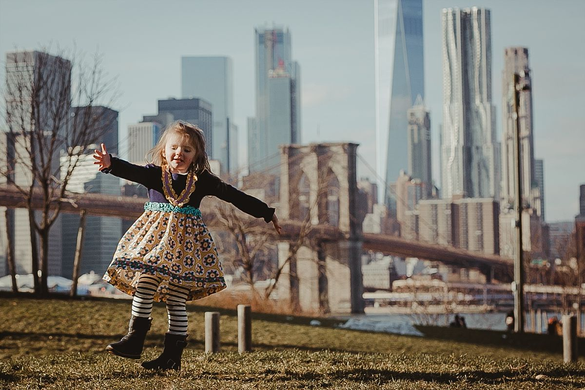 candid image of young girl dancing on green grass in brooklyn with iconic views of the nyc skyline in the background. image by nyc family photographer krystil mcdowall