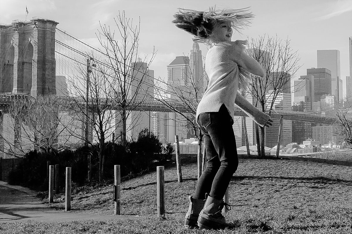 candid image of daughter dancing on grass in brooklyn with iconic views of the nyc skyline in the background. image by nyc family photographer krystil mcdowall
