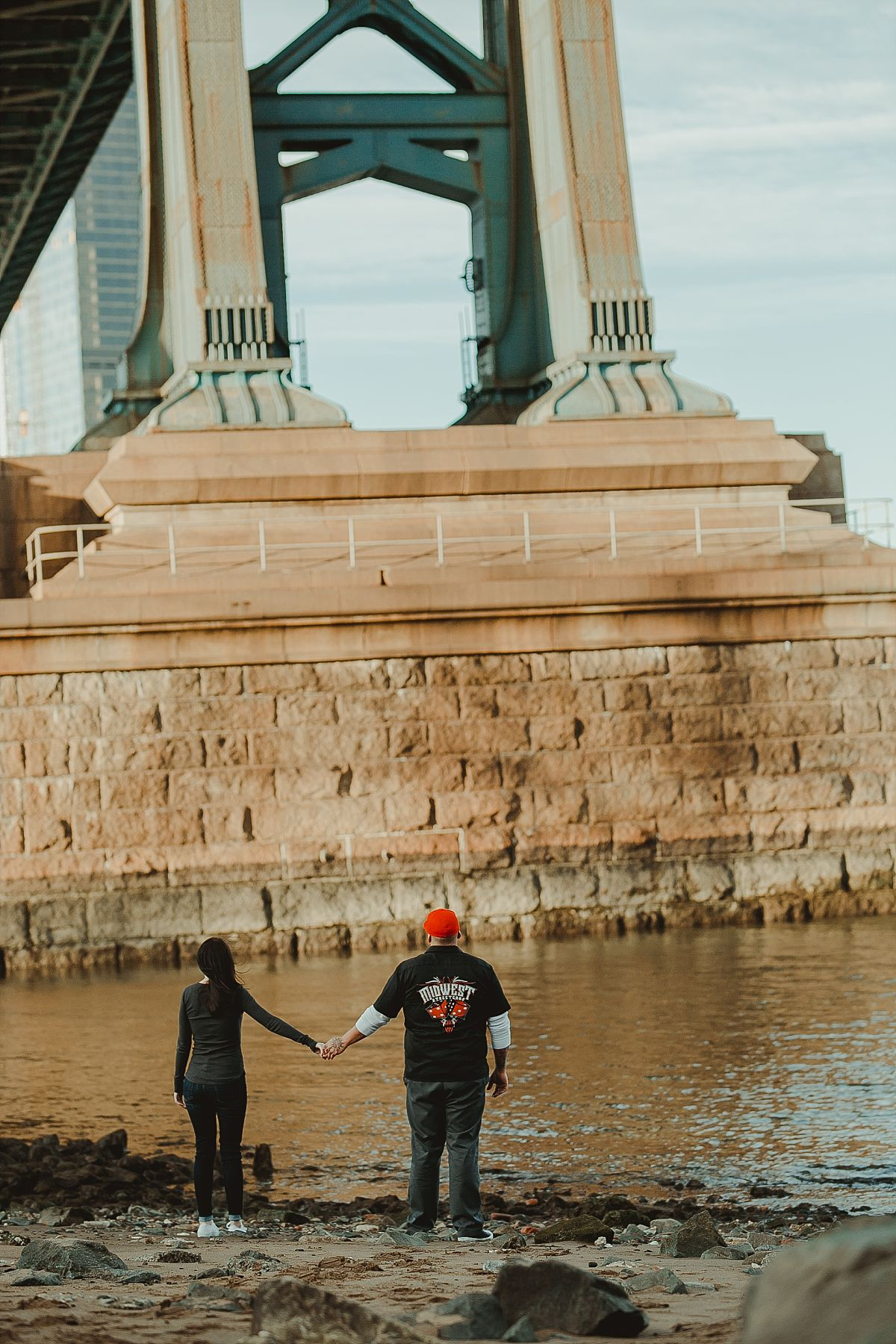 photo of couple standing underneath the manhattan bride in dumbo brooklyn during couples photoshoot. krystil mcdowall photography takes candid family photos
