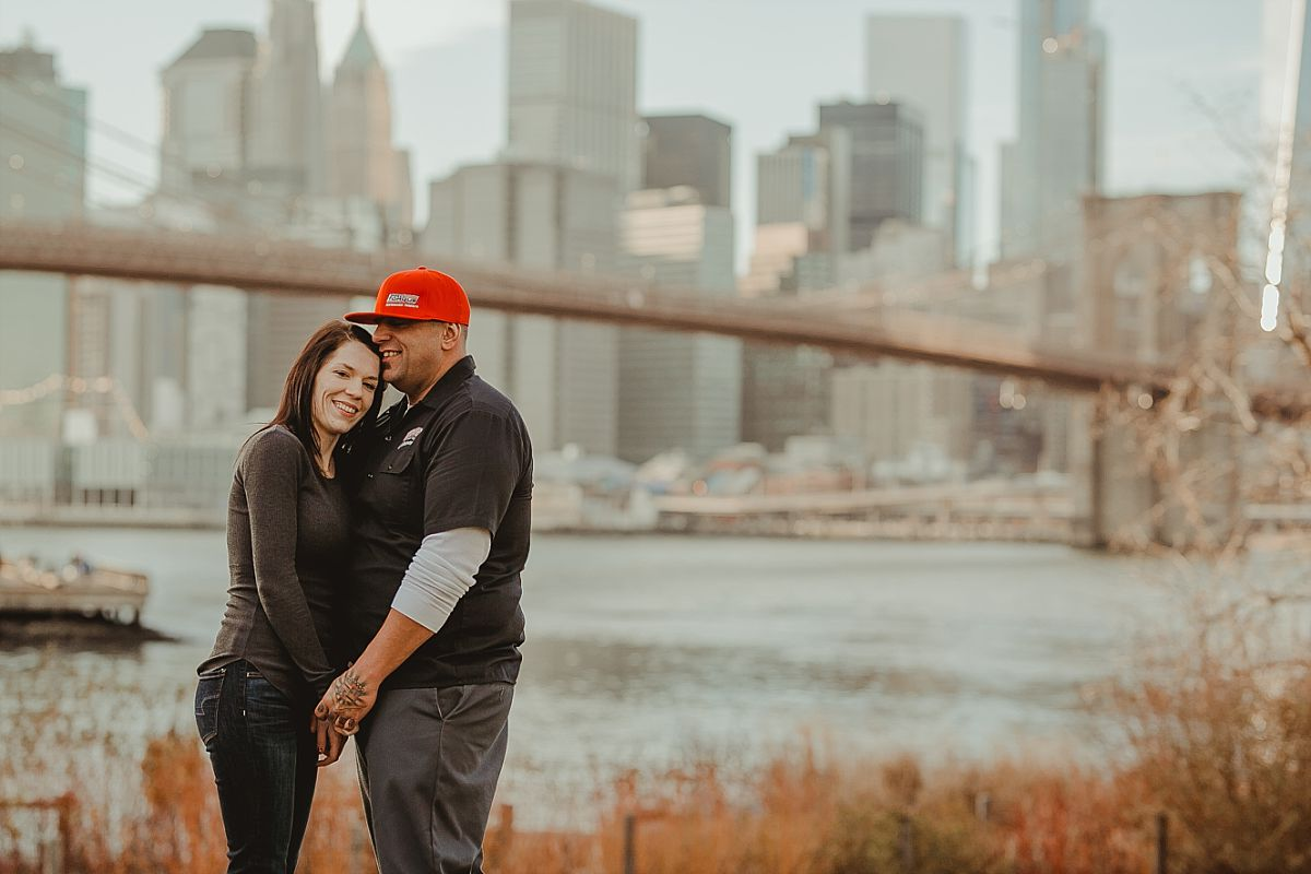 couple posed on green grass in dumbo brooklyn while beautiful manhattan skyline and brooklyn bridge appear in the background. image by nyc family photographer krystil mcdowall
