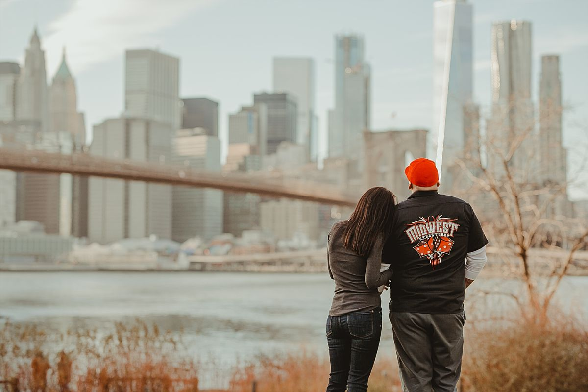 couple looks stands on green grass in dumbo brooklyn looking out at beautiful manhattan skyline and brooklyn bridge. image by nyc family photographer krystil mcdowall