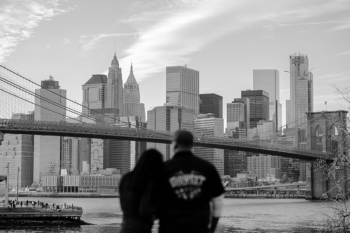 black and white image of blurred couple looking at beautiful manhattan skyline and brooklyn bridge. image by nyc family photographer krystil mcdowall