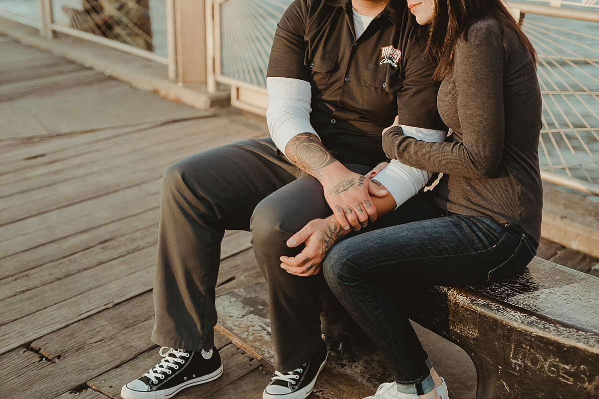 couple rests for a slow embrace at pier in brooklyn bridge park with brooklyn bridge in the background. image by nyc family photographer krystil mcdowall