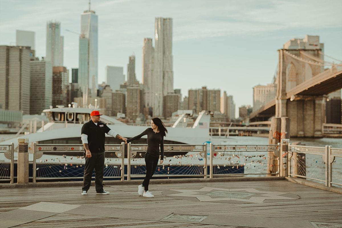 couple walks along pier in brooklyn bridge park with manhattan skyline and brooklyn bridge in the background. image by nyc family photographer krystil mcdowall