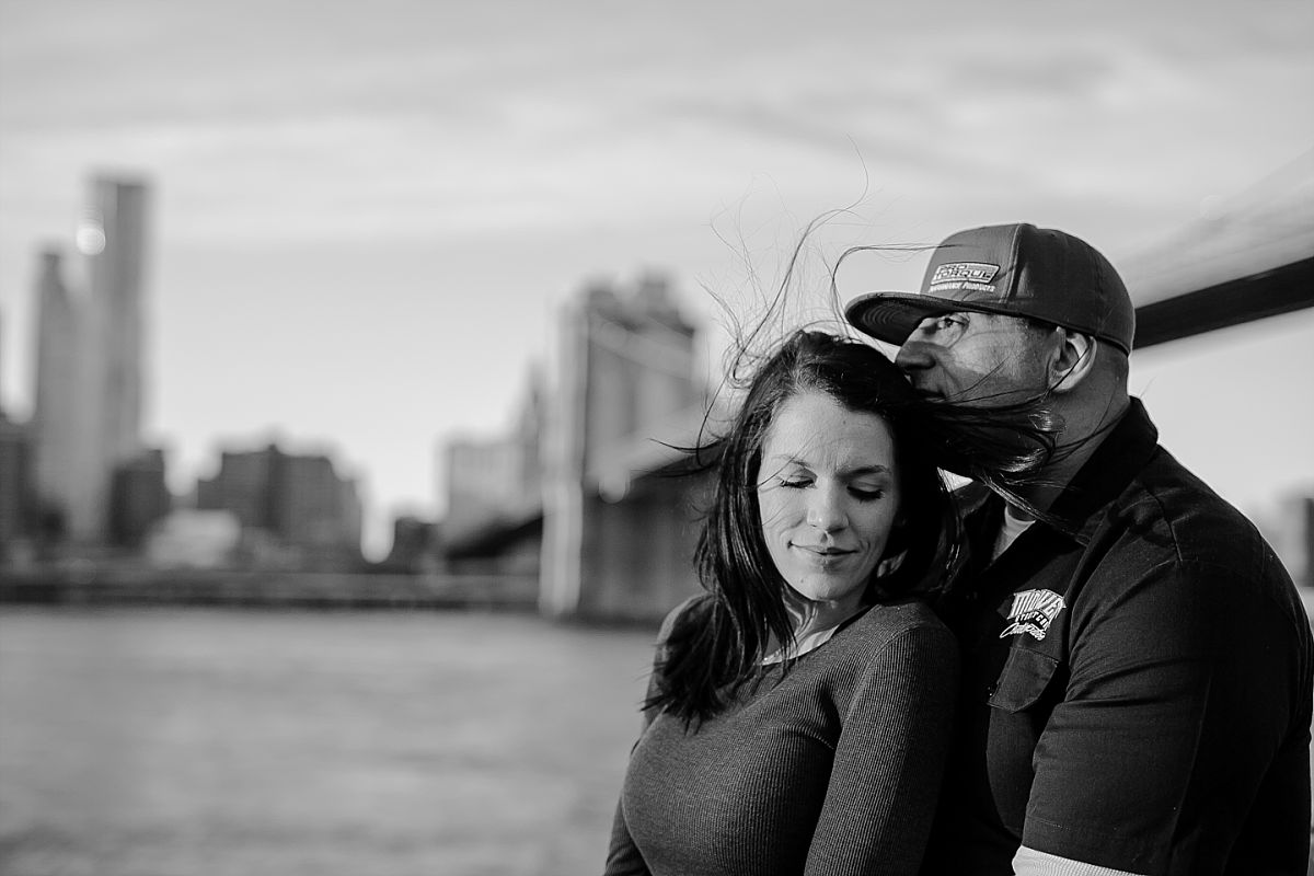 couple embraces for a quiet moment at pier in brooklyn bridge park with brooklyn bridge in the background. photo by nyc family photographer krystil mcdowall