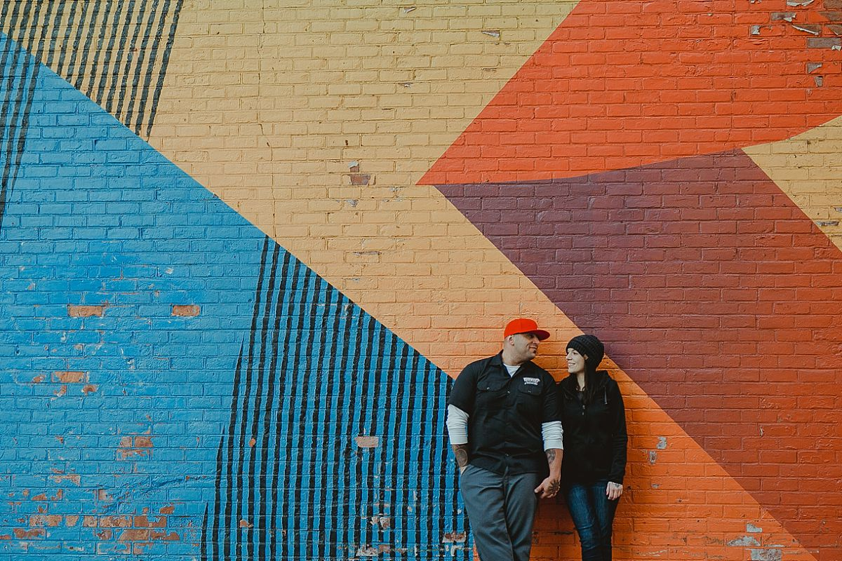 couple holds hands and stands in front of colorful graffiti mural in brooklyn. photo by nyc family photographer krystil mcdowall