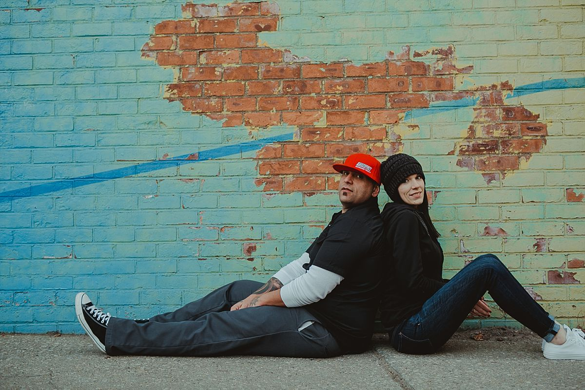 couple sits in front of blue and green graffiti mural in brooklyn. photo by nyc family photographer krystil mcdowall