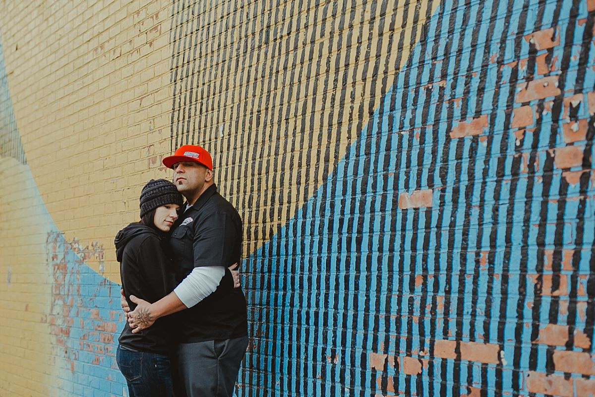 portrait of girlfriend leaning head on boyfriend's chest in front of graffiti mural in brooklyn. photo by nyc family photographer krystil mcdowall