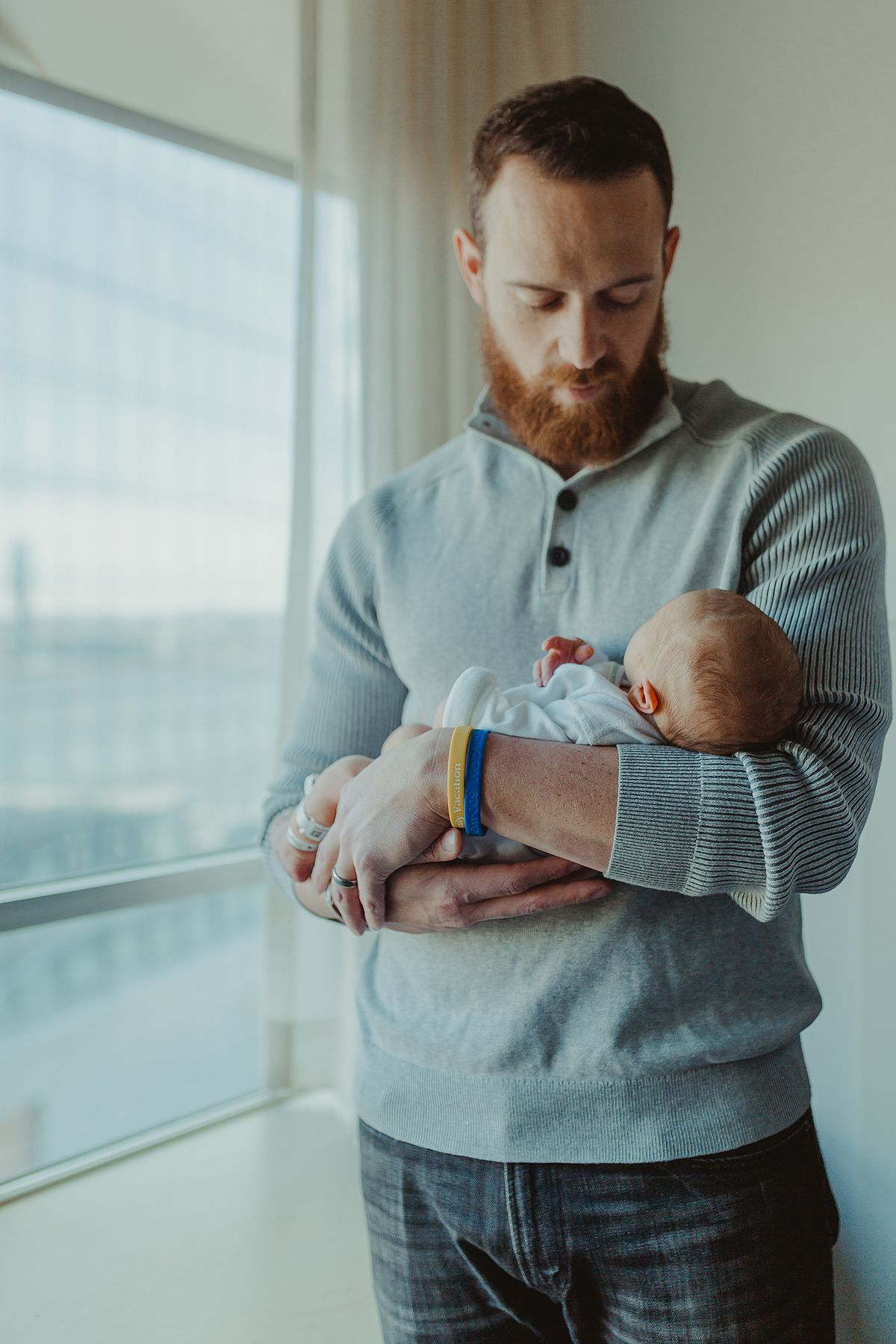fresh 48 photo of newborn baby boy and his dad standing by bright nyc hospital window when baby was 2 days old. photo by nyc family and newborn photographer krystil mcdowall