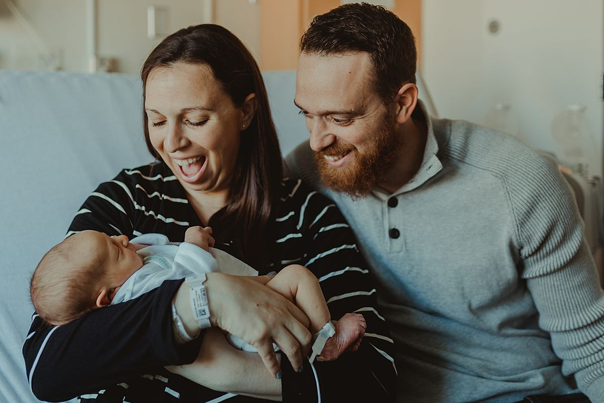 fresh 48 family portrait of mom and dad smiling at newborn son while sitting on hospital bed in manhattan nyc. photo by nyc family and newborn photographer krystil mcdowall