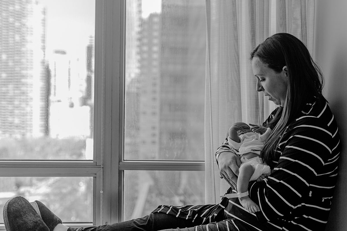 fresh 48 photo of mom holding newborn son while sitting in hospital window and looking at son lovingly. photo by nyc family and newborn photographer krystil mcdowall