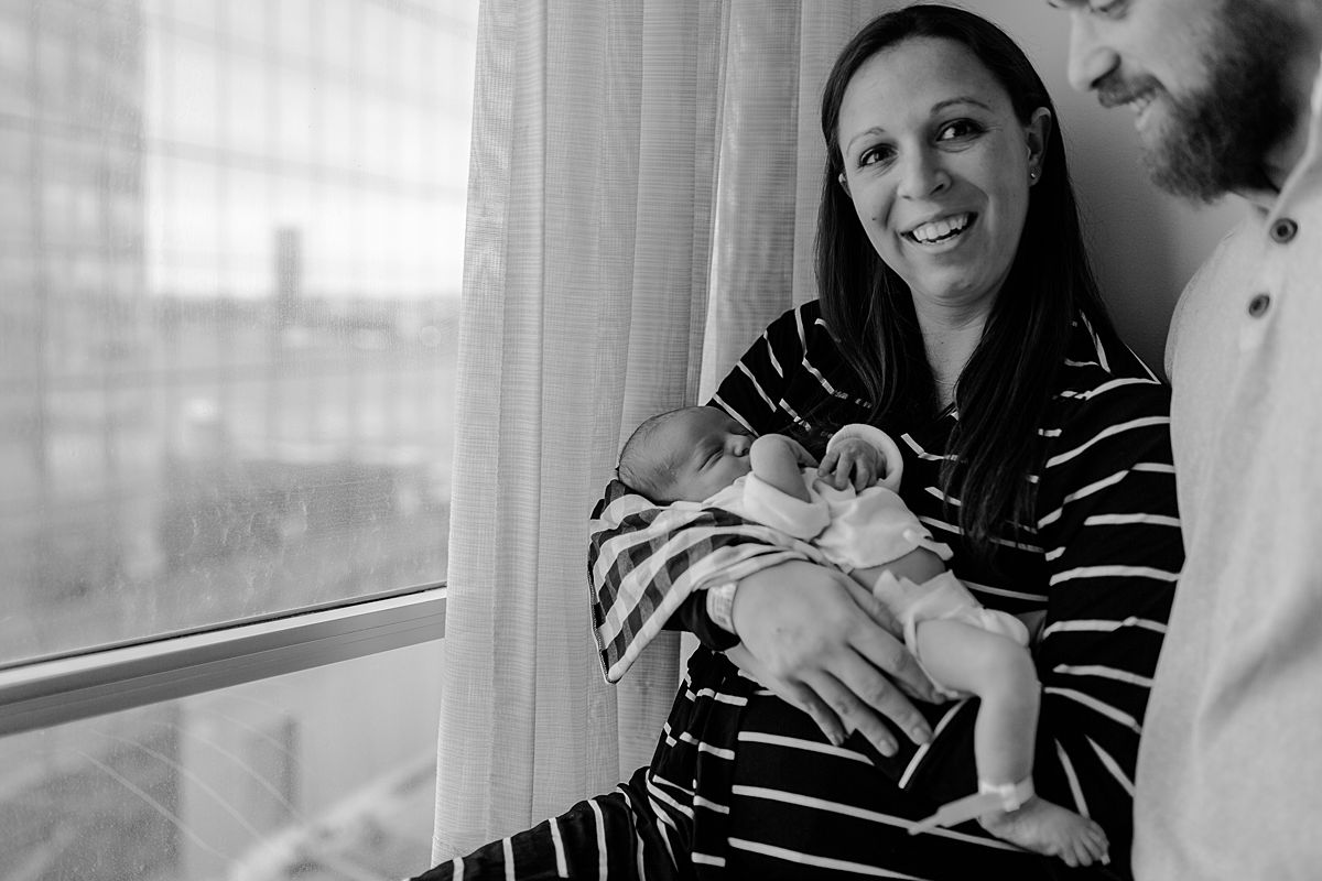 candid fresh 48 photo of mom holding newborn son with dad onlooking in nyc hospital in manhattan. photo by nyc family and newborn photographer krystil mcdowall