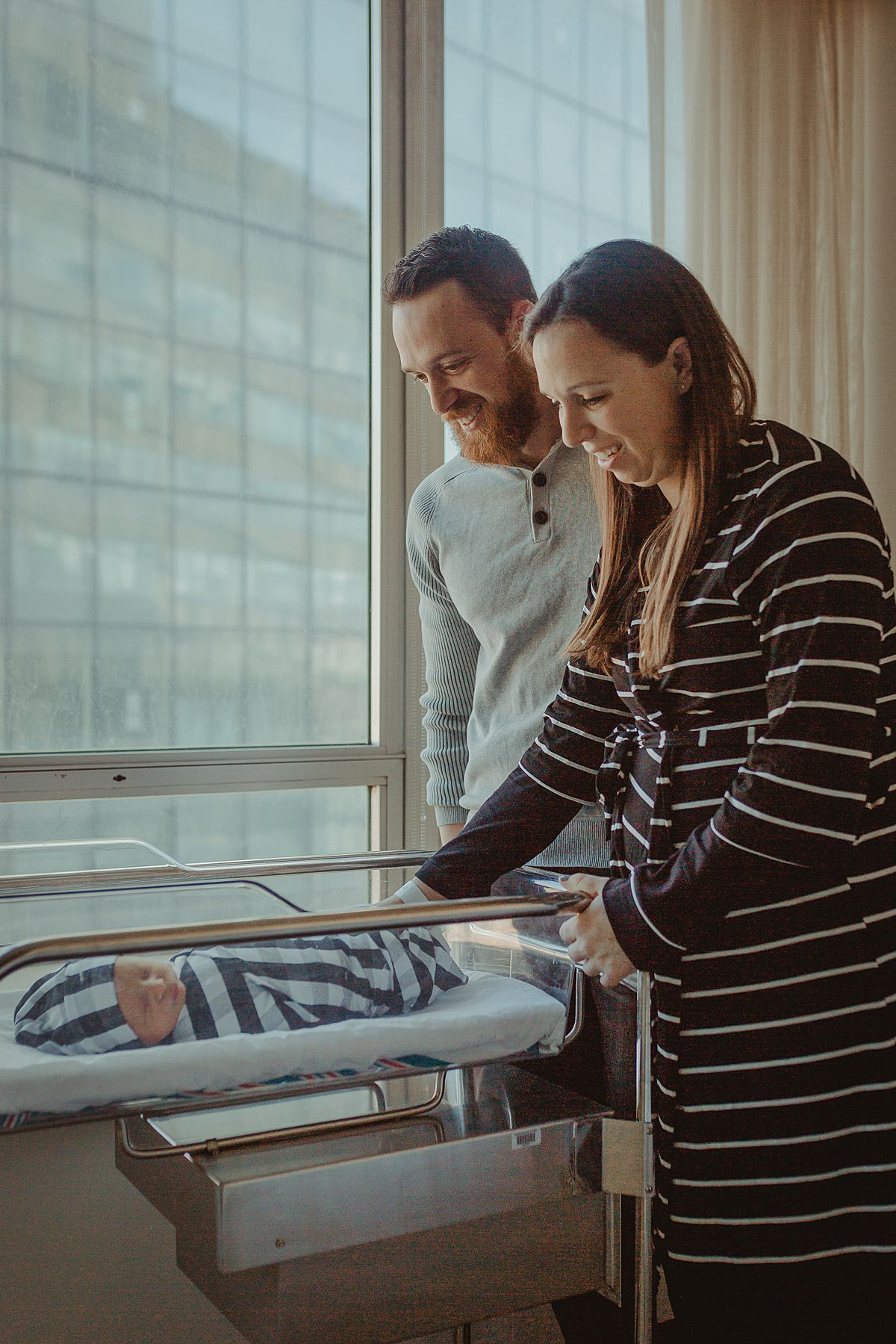 fresh 48 photo of mom and dad looking on newborn son adoringly as he sleeps in hospital bassinet in nyc fresh 48 photo shoot in manhattan nyc. photo by nyc family and newborn photographer krystil mcdowall
