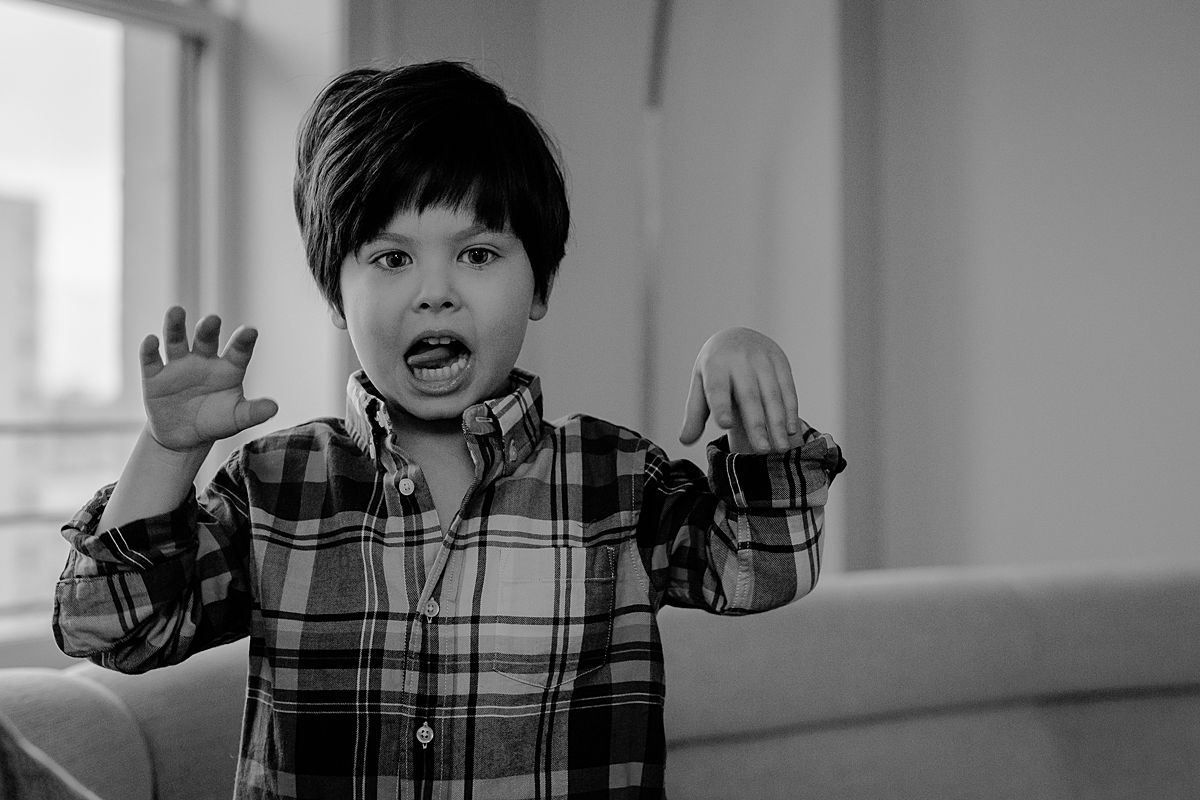 candid silly photo of young boy sticking out his tongue while playing in living room of nyc apartment. photo by nyc family and newborn photographer Krystil McDowall